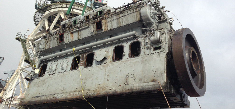 Engine block of the dredge being removed from the vessel.